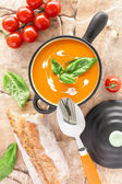 Tomato soup in a black casserole, drizzled with cream and garnis — Stock Photo