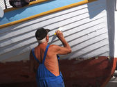 Senior painting boat — Stock Photo