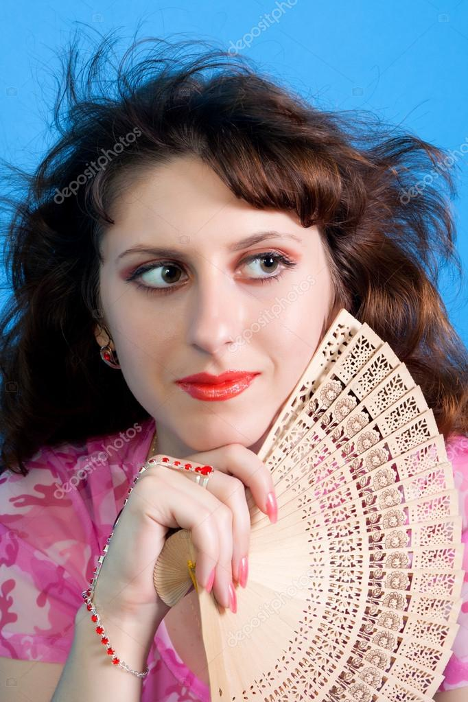 Portrait of beautiful brunette woman with fan in hands — Stock Photo #15869011