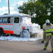 Постер, плакат: Firefighters extinguish a fire in a burning bus