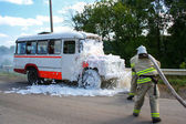 Firefighters extinguish a fire in a burning bus — Stock Photo