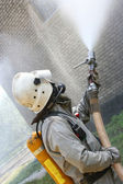 Fireman spraying water — Stock Photo