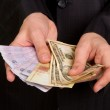 Businessman in a suit holding a money — Stock Photo