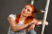 Beautiful young red-haired girl leaning on a ladder — Stock Photo