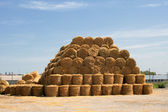 Pyramid of hay with the blue cloudy sky in the background — Stock Photo