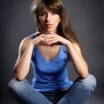 ragazza seduta nella posizione del loto in jeans su un grigio — Foto Stock