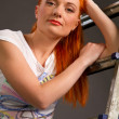 Young red-haired girl leaning on ladder on gray background — Stock Photo #21627183