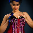 Girl in a red corset on a dark background — Stock Photo