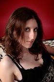 Jonge brunette in een elegante jurk op een rode achtergrond — Stockfoto