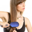 Young woman combing her long brown hair with hairbrush — Stock Photo #22173349