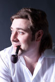 Young man smoking a pipe — Stock Photo