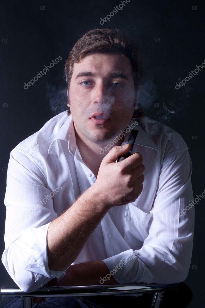 年轻美丽的男人抽着烟斗的艺术黑暗肖像
