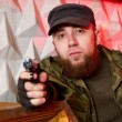 terrorist with a gun in the stroma of a dilapidated shelter — Stock Photo