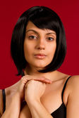Sexy brunette on red background — Stock Photo