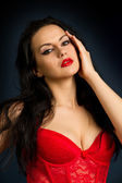 Woman in beautiful red lingerie on dark background — Stock Photo