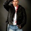 Young man in a leather jacket on a gray background — Stock Photo #33969703
