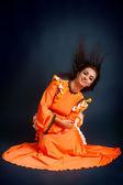 Dancer posing in traditional orange costume — Stock Photo