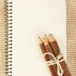Notebook and pencils on burlap — Stock Photo #9701600