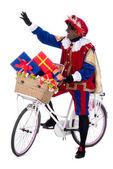 Zwarte piet auf einem fahrrad mit geschenke — Stockfoto