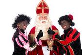 Zwarte Piet giving pepernoten (cookies) to Sinterklaas — Stockfoto