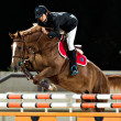 Female rider participates in horse jumping - Stock Photo