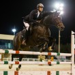 Rider competes in horse jumping competition - Stock Photo