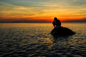Silhouette of a boy squatting on a rock fishing during sunset — Stock Photo