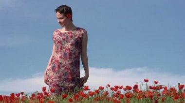 Female Model with short hair slowly walks among flowers — Stock Video