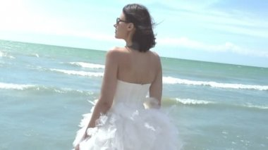 Girl in an elegant wedding dress standing on the beach — Stock Video