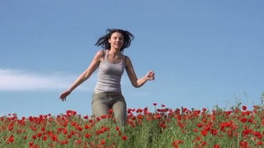 Beautiful brunette is running on the field of poppies — Stock Video