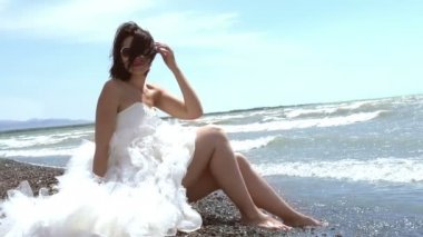 Mooie brunette in een trouwjurk zitten door de zee — Stockvideo