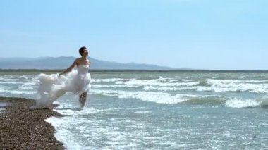 Woman in a wedding dress walking along the edge of the surf. — Stock Video