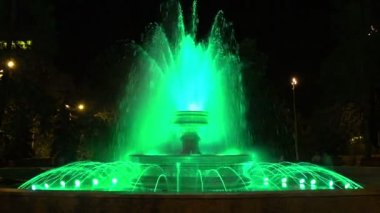 Night fountain. City fountain is illuminated with colored lights — Stockvideo