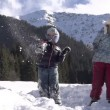 Winter Vacation. Children thrown snowballs on a background of snow-capped mountains. — Stock Video
