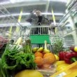Man with a shopping trolley is moving rapidly between rows in a huge store — Stock Video #45628867