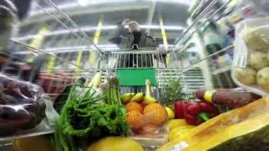 Man with a shopping trolley is moving rapidly between rows in a huge store — Stock Video