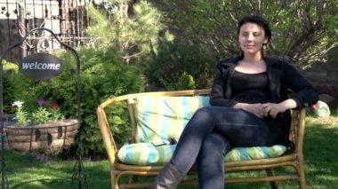 Jovem mulher senta-se num banco no jardim — Vídeo stock