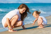 Mother playing with daughter on the beach — Stock Photo