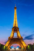 Eiffel Tower brightly illuminated at dusk — Stok fotoğraf