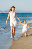 Mother and daughter walking on the beach — Stock Photo