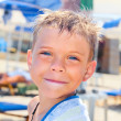 Smiley seven years old boy on the beach - Stock Photo