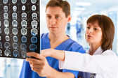 Two doctors with tomogram in hospital's corridor — Stock Photo