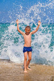 Little boy on the beach with big splashes — Foto Stock