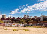 Steel industrial complex and fence with graffiti — Stock Photo