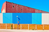 Industrial warehouse and coloured fence — Stock Photo