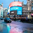 Stock Photo: Piccadilly Circus neon signage reflected on street with taxy