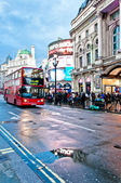 Piccadilly Circus neon signage reflected on street with bus — Stock Photo