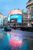 Piccadilly Circus neon signage reflected on street with taxy — Stock Photo