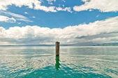 Lonely pole in garda Lake — Stock Photo