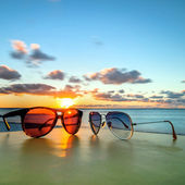 Sunglasses on tropical beach table at sunset — Stock Photo